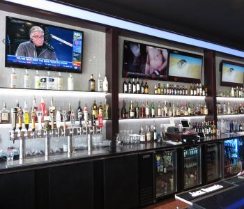 image of a bar inside a restaurant with 3 big flat screen tvs above the bar