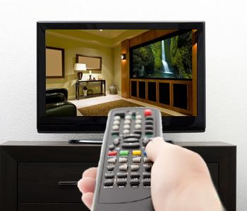 a hand holding a remote turning on a tv