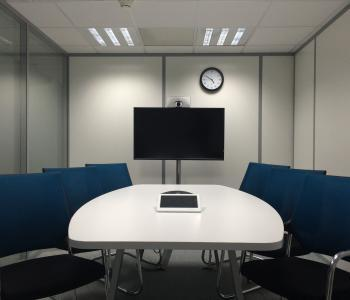 conference room with one white table with a tablet on it and a mounted tv on a wall across from the table