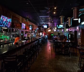photo of a bar view with the bar and a tv on the left and other seating on the right
