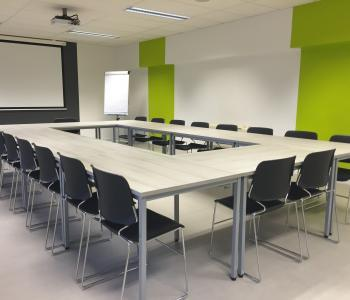 photo of a conference room with black chairs around a big table and a projector screen at the further end