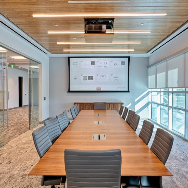 conference room with ceiling mounted projector and screen